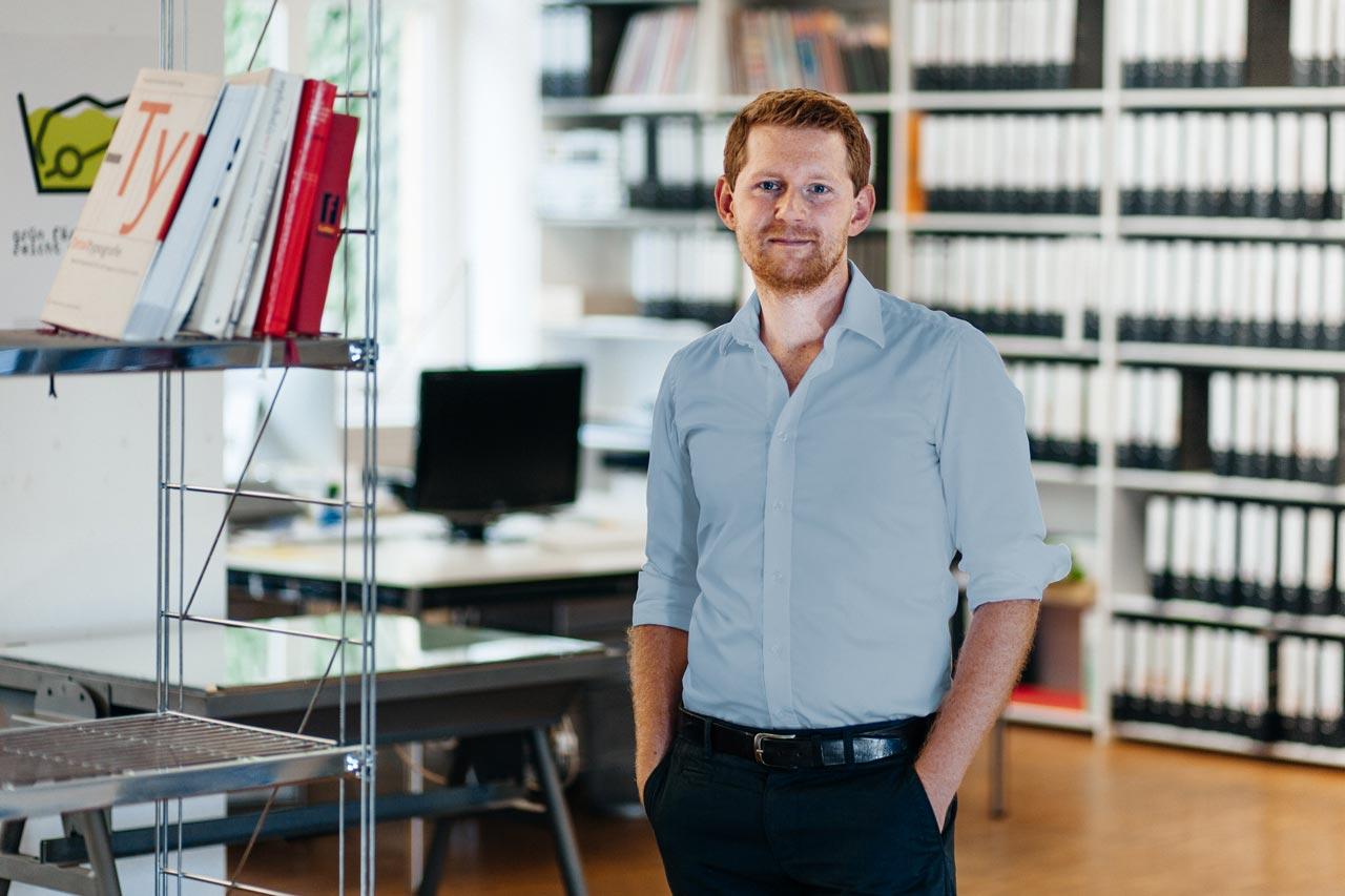 Ein junger Mann steht in einem Büro. Im Hintergrund steht ein Schreibtisch mit einem Monitor und Regal mit vielen Aktenordnern.