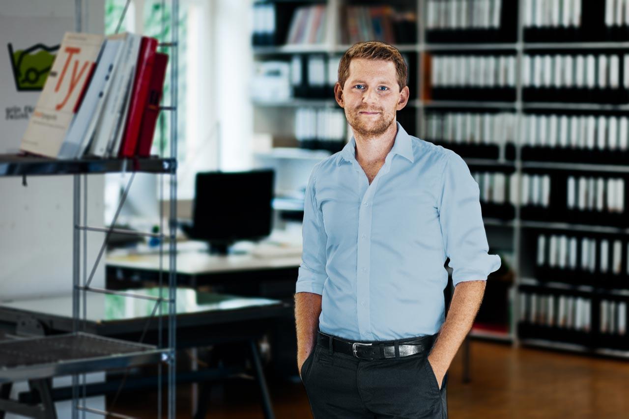 Gleicher Bildinhalt wie im ersten Bild: Ein junger Mann steht in einem Büro. Im Hintergrund steht ein Schreibtisch mit einem Monitor und Regal mit vielen Aktenordnern.